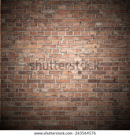 red brick wall texture background with beam of spot light dark vignette - stock photo
