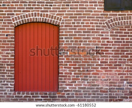 Red Brick Wall with a Red Door and Window - stock photo