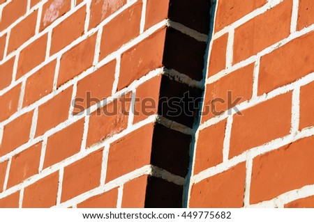 Red brick wall with white seams. The wall is lit with a sunlight a ledge on a wall in a shadow - stock photo