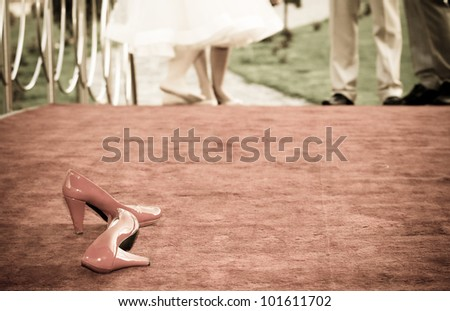Red bridal shoes and barefoot bride in the background - stock photo