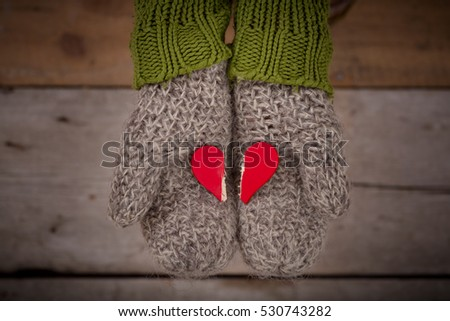 red broken heart in hands in gray gloves on wooden background