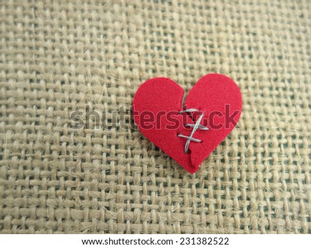 Red broken heart stitched with thread                                - stock photo