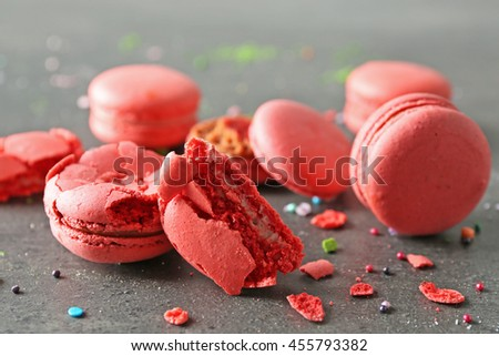 Red broken tasty macaroons on gray background - stock photo
