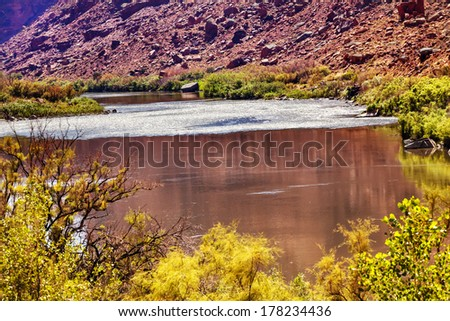 Red Brown Colorado River Reflection Abstract Green Yellow Grass Red Rock Canyon Outside Arches National Park Moab Utah USA Southwest.  - stock photo