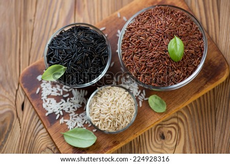 Red, brown, white and black raw rice kernels, high angle view - stock photo