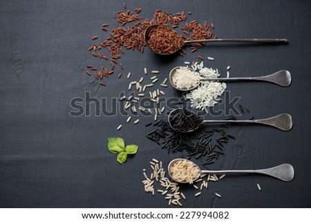Red, brown, white and black raw rice kernels, horizontal shot - stock photo