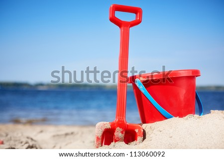 red bucket and shovel on the beach - stock photo
