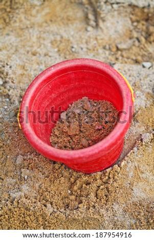 Red Bucket in the sandbox - stock photo