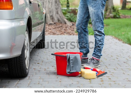 Red bucket, sponge and remain tools for cleaning the car - stock photo