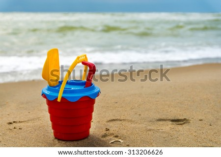 Red bucket with a shovel, a rake and a net on the beach and wet sand - stock photo