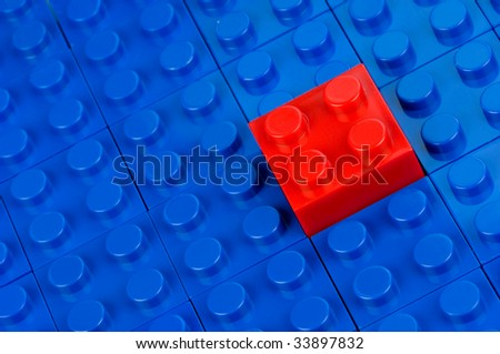 Red building block, gliding in a field of blue one