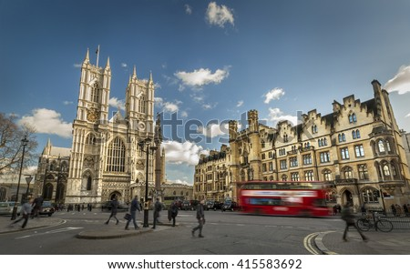 Red bus and people are moving next to the Westminster Abbey (The Collegiate Church of St Peter at Westminster) - Gothic church in City of Westminster, London. Place of coronation of English monarchs - stock photo