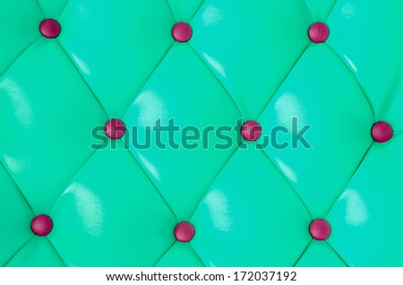 Red buttoned on the green Texture. Repeat pattern - stock photo