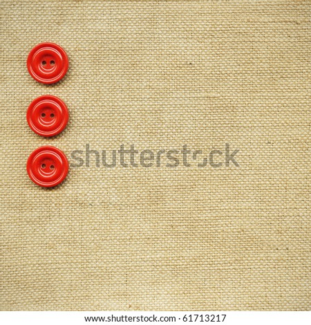 Red buttons on the beige fabric - stock photo