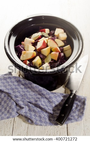 red cabbage with apple and bay leaf in a black slow cooker pot  - stock photo
