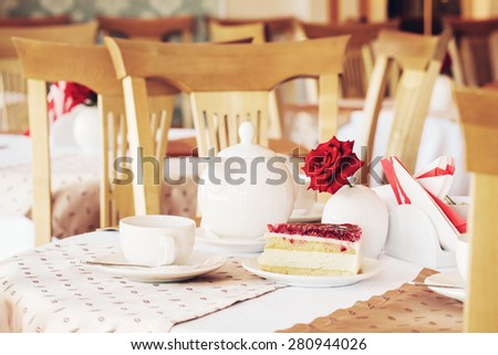 red cake and cup of tea in cafe - stock photo