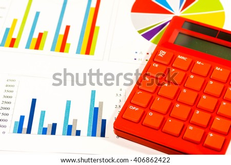 Red calculator on colorful graphs - stock photo