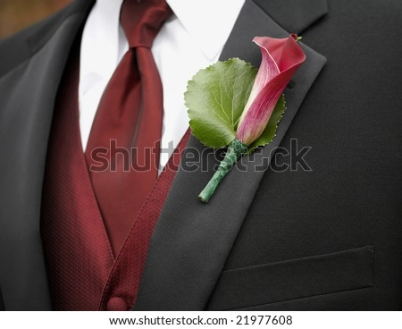 Red calla lily boutonniere on suit jacket of groom