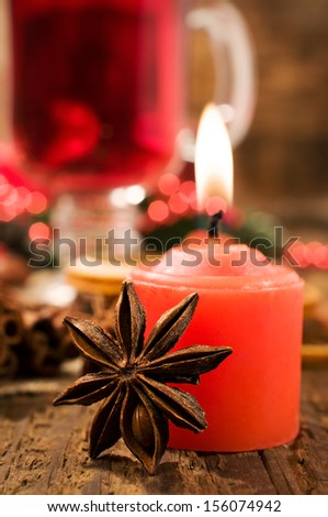 Red Candle and Christmas spices clos- up on wooden