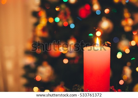 red candle burning in a beautiful candlestick near the Christmas tree
