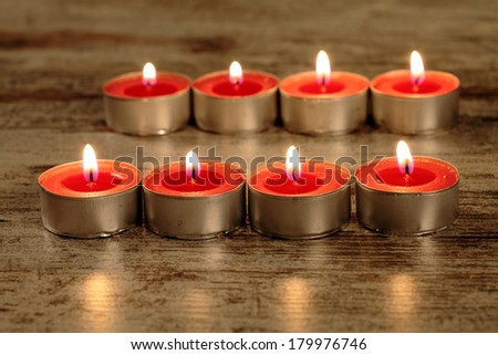 red candle on a wooden floor