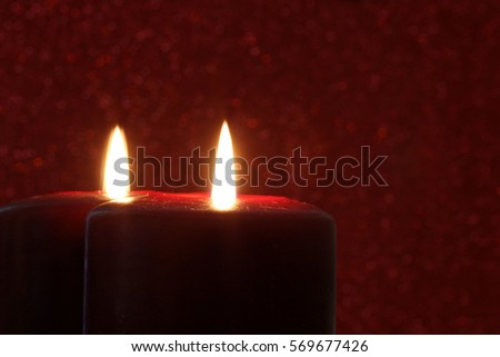 Red Candle Reflected in Mirror with Red Glitter Background - Photograph of a red burning candle reflected in a vintage mirror with a red sparkling background.  Selective focus on the front candle.
