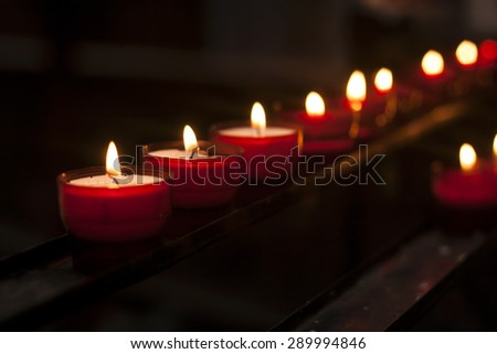 red candles in the darkness of a church