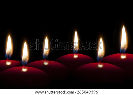 red candles lighting in the darkness or in a black background