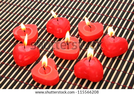 Red candles on wooden math.