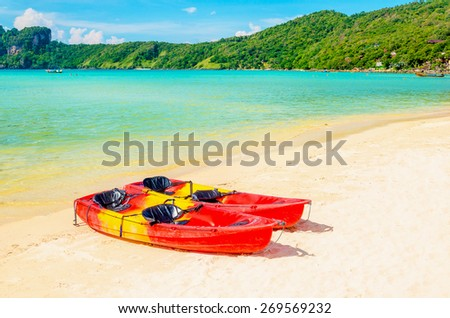 Red canoe on a beautiful sandy beach  - stock photo