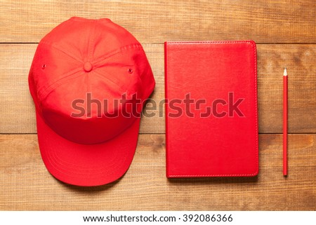 Red cap, dairy and red pencil on wooden background - stock photo
