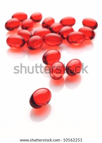 Red capsules on white background - stock photo