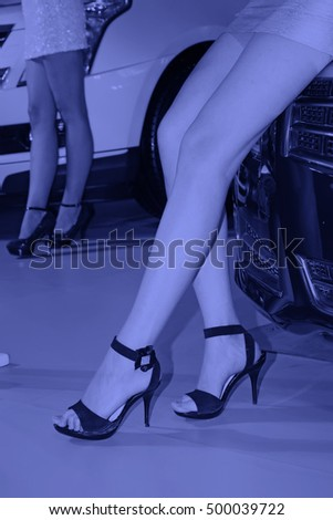 red car black high heels in a auto show