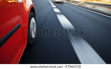 Red car driving at high speed in the highway