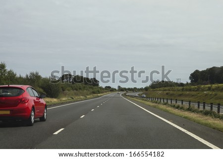 Red car driving on the left side of a quiet motorway - stock photo