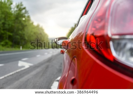 Red car on the road.  Focus on the car door handle. - stock photo