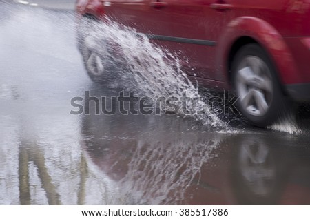 Red car rides on big puddle. Water splash.