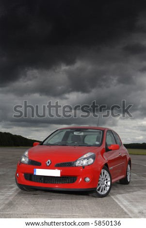 red car under dark storm clouds - stock photo