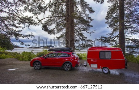 RED CAR WITH TINY CAMPER TRAILER CAMPING IN VANCOUVER ISLAND, BRITISH  COLUMBIA, CANADA