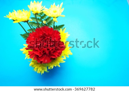 Red carnation and yellow flowers with blue background. Focus on red flowers. Space for texts. - stock photo