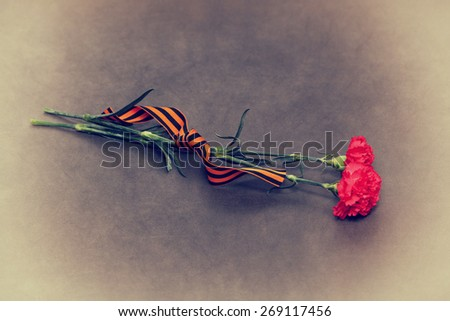 Red carnation flowers and George Ribbon on an abstract background. Vintage Photo. In honor of the victory in World War II - stock photo