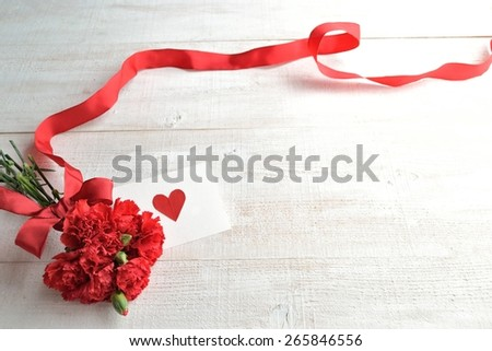Red carnations bouquet with message card - stock photo