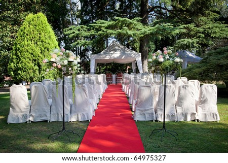 Red carpet and chairs for an outdoor wedding - stock photo