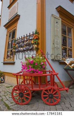 Red cart with a flower pot - stock photo