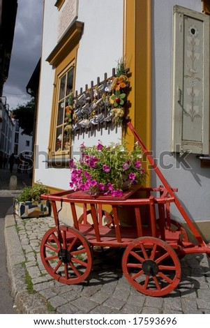 Red cart with a flower pot. Photographed in Erfurt (Germany) - stock photo