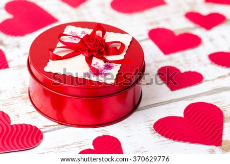 Red casket with hearts on a wooden background