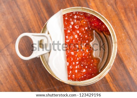 red caviar in bank with spoon on wood background - stock photo