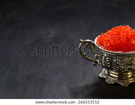 Red caviar in silver bowl. Selective focus, copy space background - stock photo