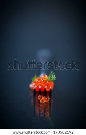 red caviar on a fork on black background - stock photo