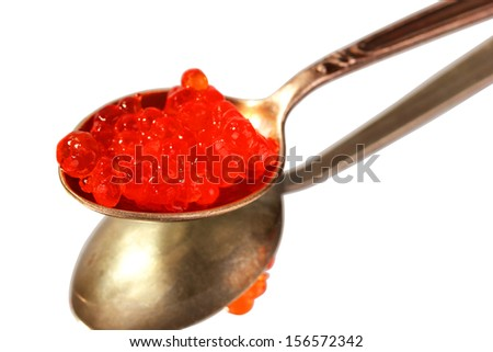 Red caviar on a silver spoon. White background